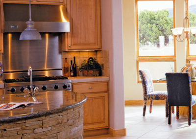 Round Kitchen Countertop Island With Hooded Range In Background